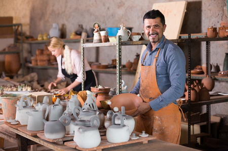 happy russian  man and woman potters holding ceramic vessels in atelier Imagens
