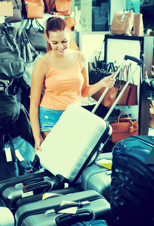 glad teenager girl choosing new large plastic luggage bag in store 版權商用圖片