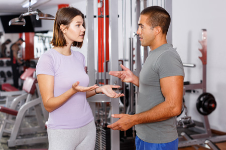 Young sporty man and woman talking emotionally at gym Stock Photo