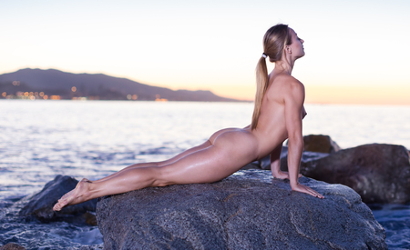 Nude female is lying on a rock near the sea at the dawn