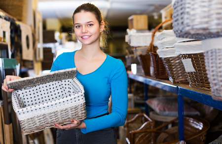 cheeful young customer standing with wicker basket in shop for decor