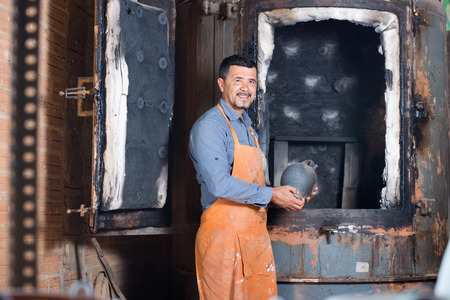 Cheerful diligent craftsman carrying fresh baked black glazed vessel in ceramics atelier