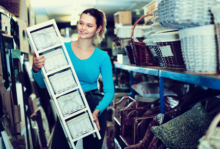 Happy cheerful  young woman consumer with nightstand with basket in decor items store Standard-Bild - 123017811