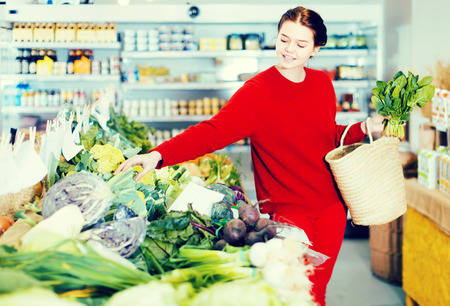 cheerful young woman choosing seasonal vegetables in farm food store Standard-Bild - 123017823