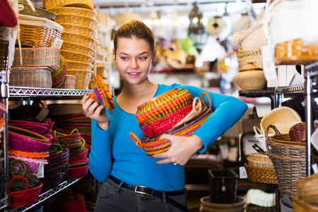 Female teen  choosing colour wicker basket in decoration and store Standard-Bild - 123017827