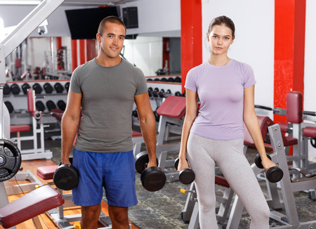 Portrait of cheerful couple doing exercises with dumbbells at gym Standard-Bild - 123017840