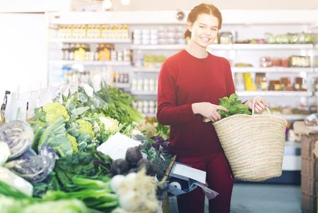 happy young woman choosing seasonal vegetables in farm food store Standard-Bild - 123017848