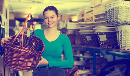 Young woman  purchaser standing with picnic basket in shop for decor Standard-Bild - 123017860