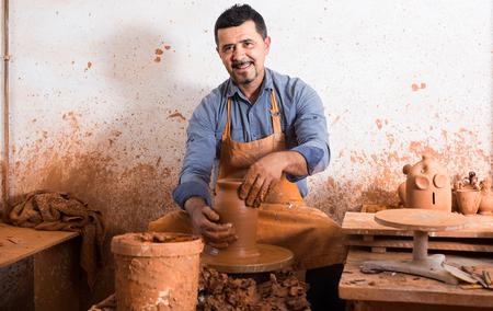 Feliz hombre artesano ruso creando pieza de cerámica en torno de alfarería en el taller