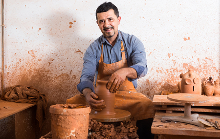 happy russian artisan man creating ceramic piece on spinning pottery wheel in workshop