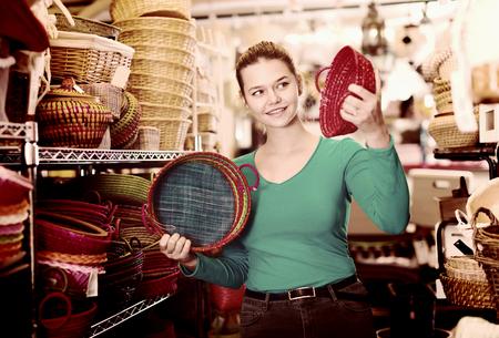 Nice female teen  choosing colour wicker basket in decoration and store 版權商用圖片