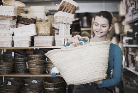 Laughing female  buyer choosing wicker bag in decoration and store