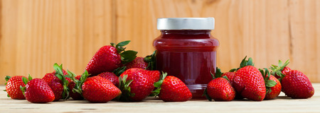 Closed glass jar of homemade jam of strawberry with fresh berries on wooden background