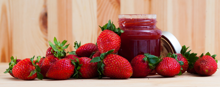 Tasty sweet homemade strawberry jam in glass jar and ripe berries on wooden surface