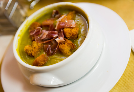Zucchini cream soup with crispy croutons and dry cured ham shavings. Spanish cuisine
