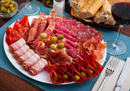 Traditional Spanish meat platter - sliced dry-cured jamon, bacon and sausages on round serving plate with olives