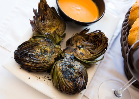 Plate of tasty Catalonian dish - grilled artichokes with romesco sauce Reklamní fotografie