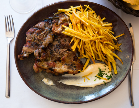 Appetizing roasted lamb meat with French fries and white sauce