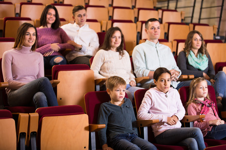 Numerous audience attentively watching a movie in cinema house