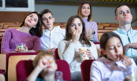 Number of happy friendly people enjoying film screening and popcorn in cinema 版權商用圖片