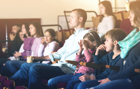 Number of young people enjoying interesting film screening in cinema house