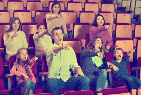 Number of glad positive people enjoying exciting film in in cinema house