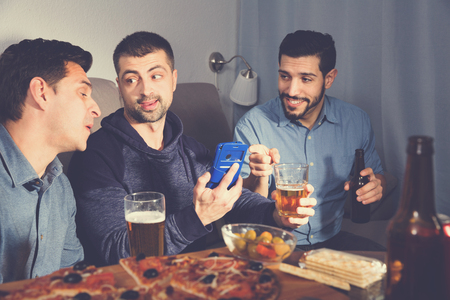 Happy  positive smiling male friends sitting with phone at home, enjoying time together