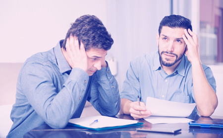 Two upset male friends looking worriedly at papers at home table Standard-Bild - 122932228