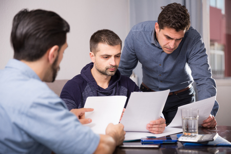 Three upset male friends looking worriedly at papers at home table