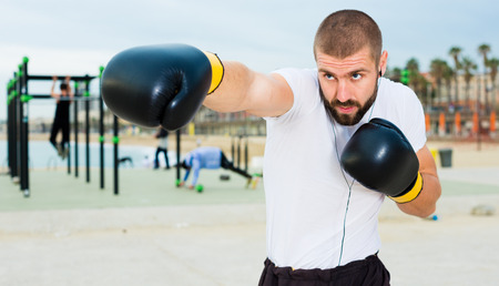 Athletic man in boxing gloves fulfills blows under the open sky Reklamní fotografie