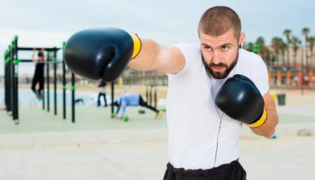 Athletischer Mann in Boxhandschuhen erfüllt Schläge unter freiem Himmel Standard-Bild