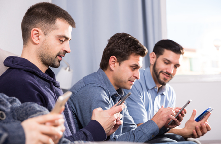 Three young men sitting with smartphones in home interior Standard-Bild - 122935232