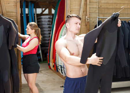Young athletic man selecting wetsuit for surfing in surf club