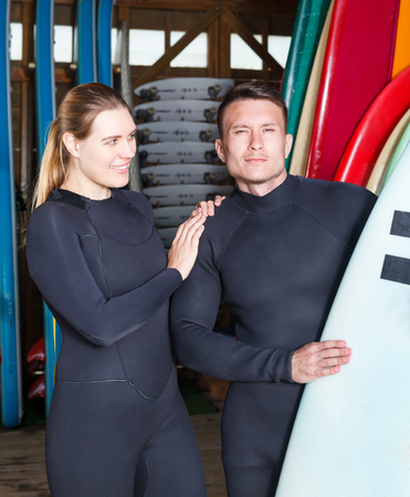 Portrait of smiling  athletes guy and girl with boards for surfing