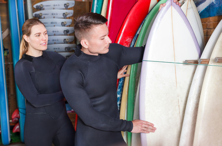 Young man and woman dressed surfing suits checking surfboards on racks at surf club. Focus on man