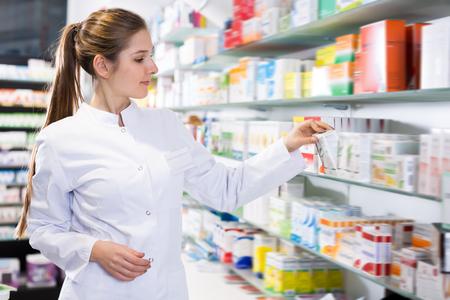 Specjalistka z uwagą szuka leków w pobliżu półek w aptece Zdjęcie Seryjne