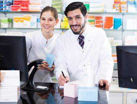 Los farmacéuticos masculinos y femeninos son un remedio de inventario atento con una nota cerca de la computadora en la farmacia.