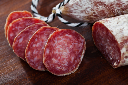 Spanish longaniza salami sausages cut in slices on a woodefn desk, close-up