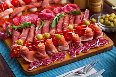 Cold cuts from Spanish ham, spicy dry-cured sausages and bacon with olives, cherry tomatoes and arugula on wooden plate
