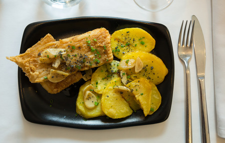 Top view of pan fried skate wings and potatoes baked with garlic . Traditional Spanish dish from Santurtzi