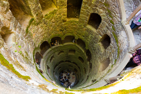 SINTRA, PORTUGAL - APRIL 21, 2019: View from top downward of spiral staircase of historical Initiation well in Quinta da Regaleira Editorial