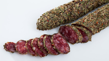 Image of spanish fuet with herbs sausages cut in slices on a  white surface, close-up Banco de Imagens