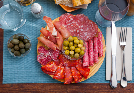 Cold smoked meat plate with traditional Spanish chorizo, fuet and salami sausages, sliced bacon and jamon Stock Photo