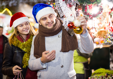 Smiling girl with boy in Christmas hat choosing decorations at market Standard-Bild - 123048154