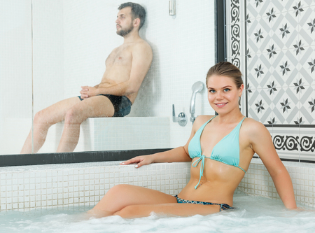 Sexy smiling young woman in turquoise swimsuit posing in jacuzzi in thermal spa Standard-Bild - 123048156