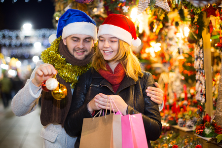 Smiling girl with boy in Christmas hat choosing decorations at market Standard-Bild - 123048157