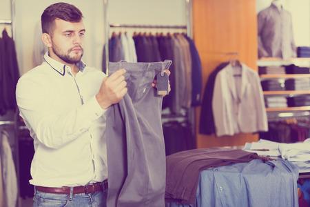 Portrait of businessman buying new pair of pants in men store Standard-Bild - 123048159