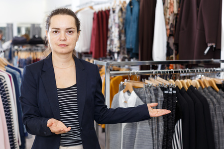 Portrait of woman in black jacket standing among clothes racks and  welcoming in clothing shop Standard-Bild - 123048162