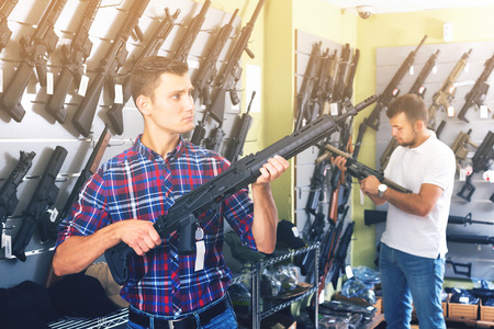 two concentrated young male friends choosing air-powered gun in army market Standard-Bild - 123048235