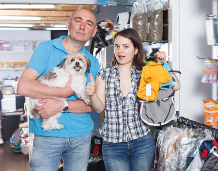 Young couple choosing for new clothes for dog in pet shop